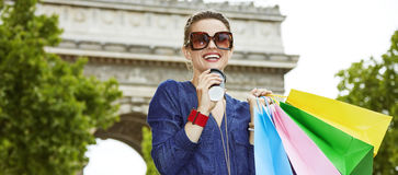 Smiling young trendy woman with shopping bags on Champ Elysees. Get your bags ready for the Paris shopping. Portrait of smiling young trendy woman in sunglasses stock photography