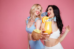 Smiling young two women dressed in swimwear drinking cocktails. Stock Photo