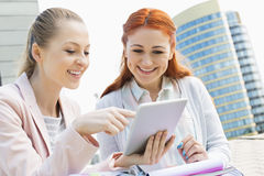 Smiling young university students using digital tablet against building Stock Image