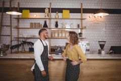 Smiling young wait staff standing at counter against shelf. In coffee shop Stock Photo