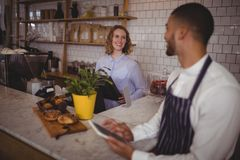 Smiling young waiter and waitress standing at counter Royalty Free Stock Photos