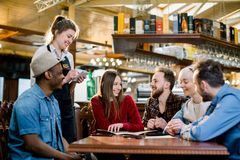 Smiling young waitress in black apron taking an order from clients in cafe. leisure, people, food cafe and holidays. Concept royalty free stock image