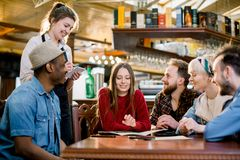Smiling young waitress in black apron taking an order from clients in cafe. leisure, people, food cafe and holidays. Concept stock photo