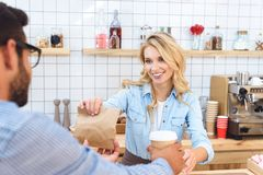 Smiling young waitress giving coffee to go and paper bag with food to client. In cafe stock photo