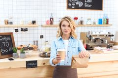 Smiling young waitress holding coffee to go in paper cup and take away food. In paper bag stock photo