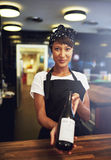 Smiling young waitress presenting a bottle of wine Stock Photo