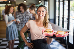 Smiling young waitress serving burger in restaurant Stock Photo