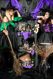 Smiling young witches with broomsticks and potions. Cauldron stock image