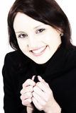 Smiling young woman. Dark haired executive woman covering up from cold in a black suit stock photography