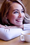 Smiling young woman. Smiling blonde young woman at the table with a cup of tea Royalty Free Stock Photo