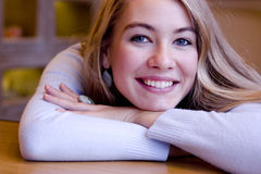Smiling young woman. Smiling blonde young woman at the table Royalty Free Stock Photos