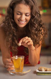 Smiling young woman adding cane sugar cube in ginger tea Royalty Free Stock Images