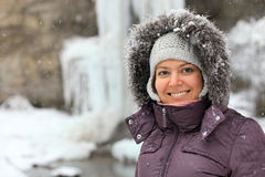 Smiling young woman against frozen waterfall Royalty Free Stock Images