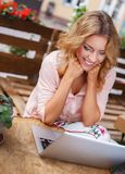 Smiling young woman alone with laptop Stock Images