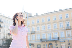 Smiling young woman answering smart phone against building on sunny day Royalty Free Stock Photography