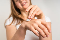Smiling young woman applying cream on her hands Royalty Free Stock Photo