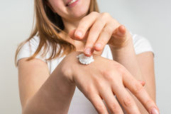 Smiling young woman applying cream on her hands Stock Photo
