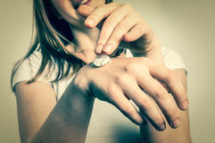 Smiling young woman applying cream on her hands Stock Images