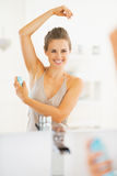 Smiling young woman applying deodorant on underarm Stock Images