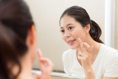 Smiling young woman applying face cream on finger. Ready smear face and looking at mirror in bathroom showing beauty skin care concept royalty free stock image