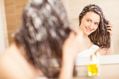 Smiling young woman applying hair mask. In front of a mirror; haircare concept stock images