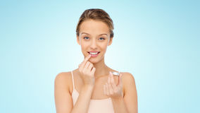 Smiling young woman applying lip balm to her lips Stock Photography