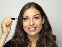 Smiling young woman applying mascara on eyelashes. Smiling young woman applying mascara on eyelashes Royalty Free Stock Images