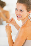 Smiling young woman applying nail polish in bathroom Stock Photography