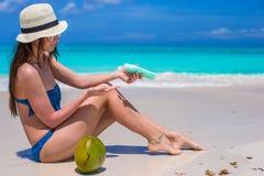 Smiling young woman applying sun cream on beach Stock Photo