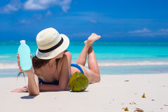 Smiling young woman applying sun cream on beach Royalty Free Stock Photos