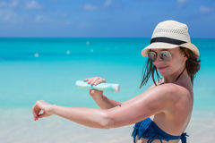 Smiling young woman applying sun cream on beach Stock Images