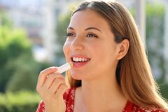 Free Smiling Young Woman Applying Sun Protection On Her Lip Outdoor Royalty Free Stock Photo - 182883715