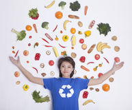 Smiling young woman with arms outstretched and fresh fruit and vegetables around her head, studio shot Stock Photography