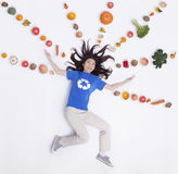 Smiling young woman with arms outstretched and fresh fruit and vegetables in lines and patterns, studio shot Stock Photo