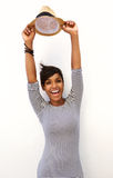 Smiling young woman with arms raised and holding hat Stock Image