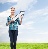 Smiling young woman with arrow poiting up Royalty Free Stock Images
