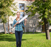 Smiling young woman with arrow poiting up Stock Photo