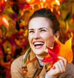 Smiling young woman with autumn leafs in front of fo Stock Image
