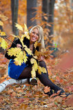 Smiling young woman in autumn park Stock Photo
