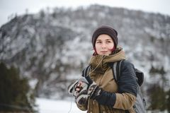 Smiling girl listening the music in winter mountains. Smiling young woman with backpack listening the music in winter mountains by white headphones stock photos