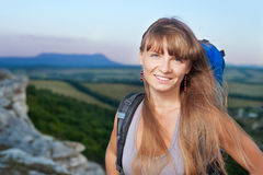 Smiling young woman with backpack in the mountains Stock Photos