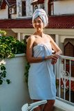 Smiling young woman in bath towel standing on hotel balcony stock photo