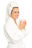 Smiling young woman in bathrobe with cup of tea Stock Photo