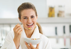 Smiling young woman in bathrobe having healthy breakfast Stock Photo