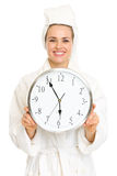 Smiling young woman in bathrobe holding clock Royalty Free Stock Photo
