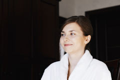Smiling young woman in bathrobe. Looking sideways while sitting on chair Stock Photography