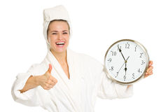 Smiling young woman in bathrobe showing clock Royalty Free Stock Photos