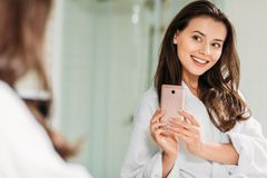 Smiling young woman in bathrobe taking selfie with smartphone at mirror. In bathroom royalty free stock images