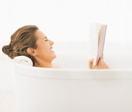 Smiling young woman in bathtub reading book Stock Images