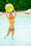 Smiling young woman with beach ball in pool Stock Photos